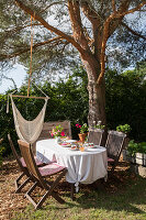 Set table with knotted tablecloth in summery garden