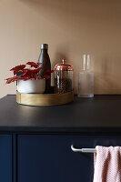 Begonia and kitchen utensils on golden tray in kitchen