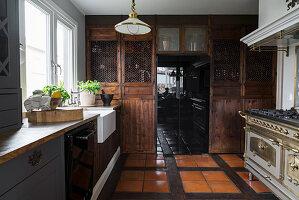 Rustikale Landhausküche mit dunklen Holzfronten und Speisekammer