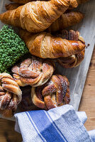 Croissants and sugared knots on wooden board