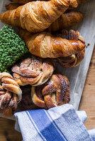 Croissant und gezuckerte Hefeknoten auf einem Brett