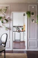 Esszimmer mit Kassettenwand und Durchgang zur Küche