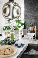 Gedeckter Tisch mit Zimmerpflanzen und selbstgemachten Brötchen