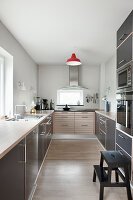 Grey, modern kitchen with accent of colour provided by red ceiling lamp