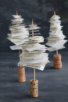 Miniature Christmas trees made form recycles book pages, skewers and corks