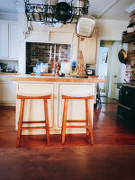 Bar stools at kitchen island below pans in rack