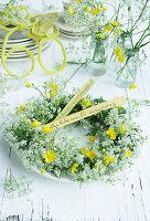 Tellerkranz aus Wiesenkerbel und Hahnenfuß als Tischdekoration zum 60. Geburtstag
