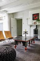 Antiker Tisch und moderne Stühle vor Kaminofen