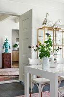 Weißer Esstisch mit Stühlen vor Vitrinenschrank und geöffneter Zimmertür