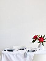 Gedeckter Tisch mit weißer Tischdecke und roten Blumen