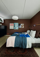 Cushions and bedspread on double bed in bedroom with brown walls