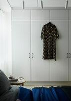 Kleid hängt an weißem Schrank im Schlafzimmer