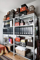 Box files, boxes and baskets in shades of black and brown on metal shelving