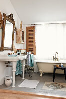 Vintage console sink below framed mirror and bathtub below window