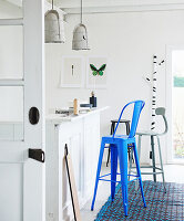 Various barstools at kitchen counter below pendant lamps