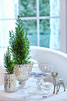 Winter arrangement of conifer in mercury silver containers