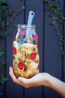 Hand holding jar of homemade apple preserve decorated with red polka-dots