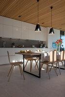 Set dining table in modern, white, open-plan kitchen