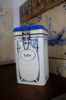 Old blue-and-white coffee can in front of old tiles