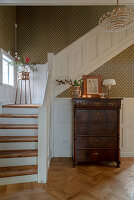 Antique chest of drawers in foyer with staircase and panelled wainscoting