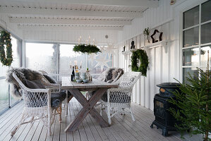 Wooden table and wicker armchairs on festively decorated veranda