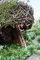Baumhaus aus Ästen in Vogelnestoptik, rustikale Leiter