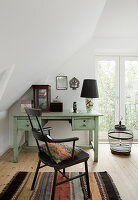 Black chair at mint-green desk below sloping ceiling