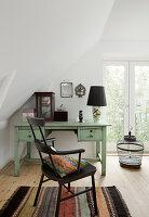 Schwarzer Stuhl vorm mintgrünen Schreibtisch unter der Dachschräge