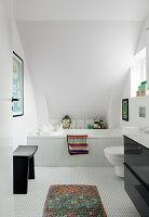 Mosaikfliesen im Bad mit eingebauter Badewanne unter der Schräge