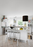 Bar stools at island counter in white, modern kitchen