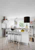 Barhocker an der Küchentheke in moderner Küche in Weiß