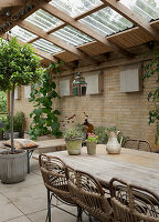 Rattan chairs at dining table in conservatory with brick walls