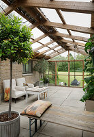 Bay tree, armchairs and bench in rustic conservatory