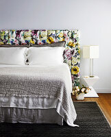 Double bed with headboard upholstered in floral fabric
