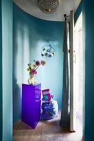 Büsten-Vase auf violettem Sockel vor blauer, geschwungener Wand