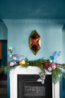 Goldene Skulptur an blauer Wand überm Kamin mit kitschiger Girlande