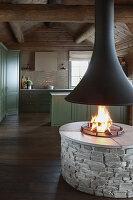 Offenes Feuer im rustikalen Wohnraum mit Landhausküche