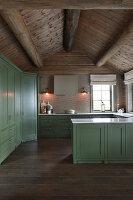 Landhausküche mit grünen Kassettenfronten im Blockhaus
