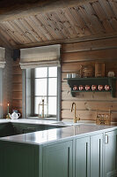 Country-house kitchen with green panelled cabinets in log cabin