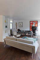 Pale sofa, armchair, shelves of CDs and multimedia trolley in living room