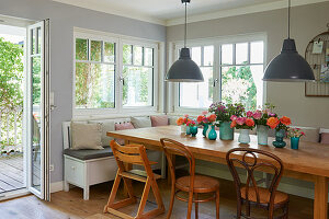 Flower arrangements on wooden table with corner bench and chairs