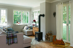 Bright upholstered suite and a wood stove in a living room