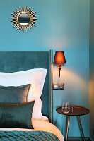 Sunburst mirror on blue wall above bed with headboard