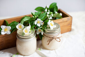 Jars of honey with sprigs of mock orange