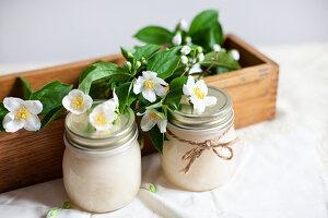 Honiggläser mit Blütenzweigen vom Bauernjasmin