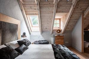 Luxuriöses Doppelbett im Schlafzimmer mit Holzdecke und Fenster