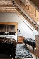 Luxuriöses Doppelbett und Hocker mit Tierfell im Schlafzimmer mit Holzdecke und Fenster