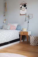 Scatter cushions on bed and bedside table below wall-mounted lamp in child's bedroom
