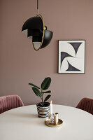 Houseplant and candle on table below lamp in dining room in earthy shades
