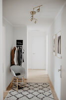 Coat rack, shell chair and rug in bright foyer